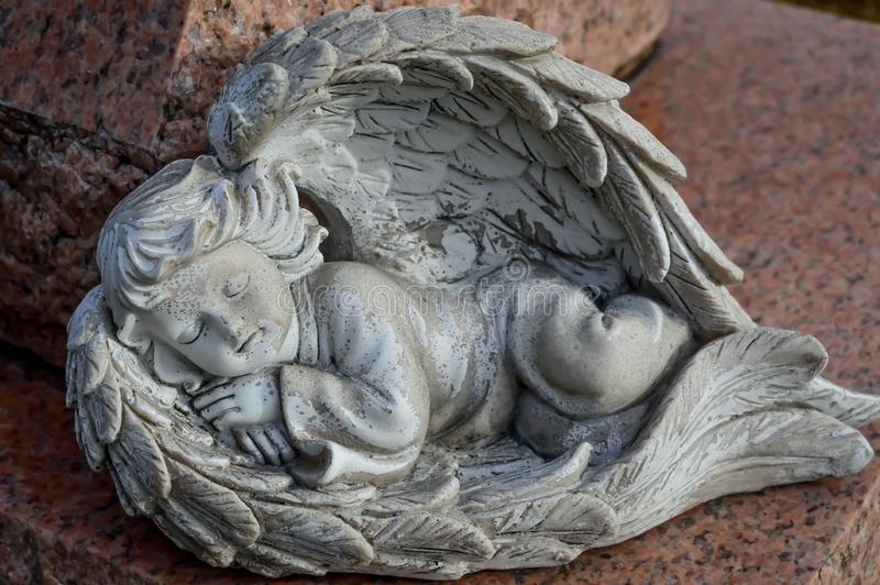 睡觉天使与翼的天使雕象床的 免版税库存图片