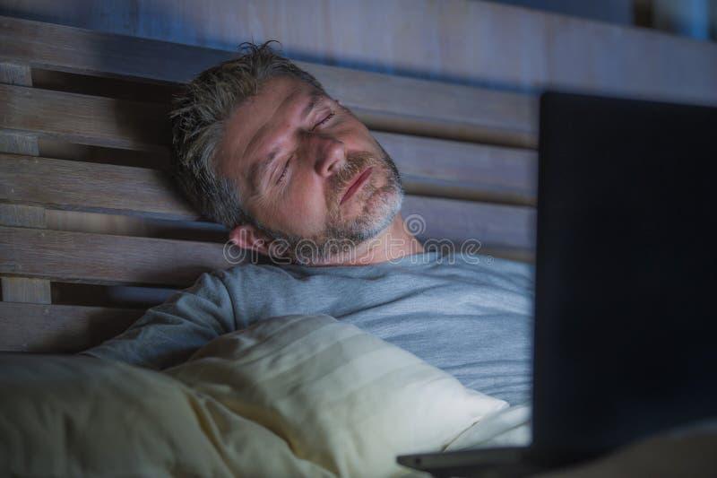 睡觉年轻疲乏和被用尽的互联网或工作上瘾者的人,当网络夜间与在床上的膝上型计算机在劳累过度或时 免版税库存照片