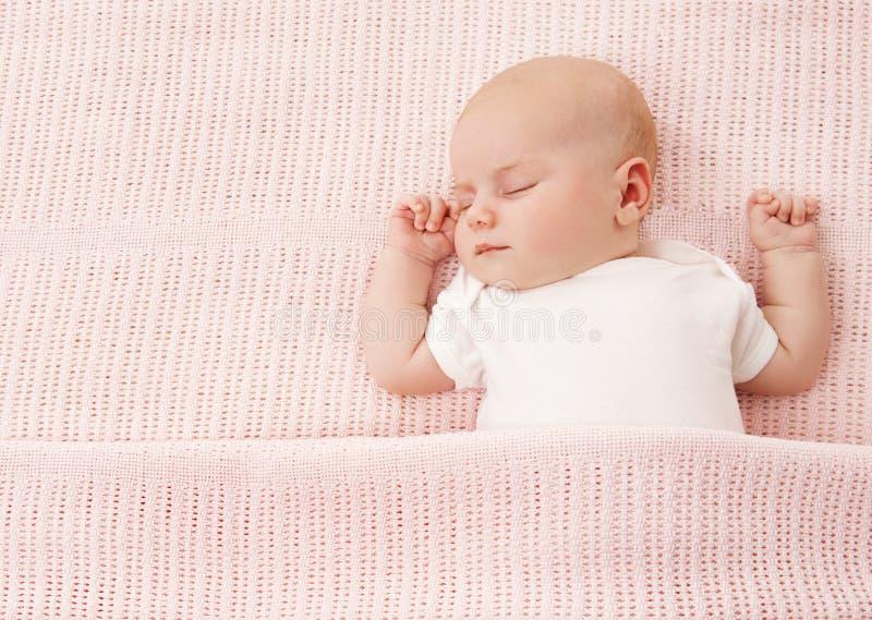 睡觉新出生的婴孩,在桃红色的新出生的孩子女孩睡眠 免版税库存图片