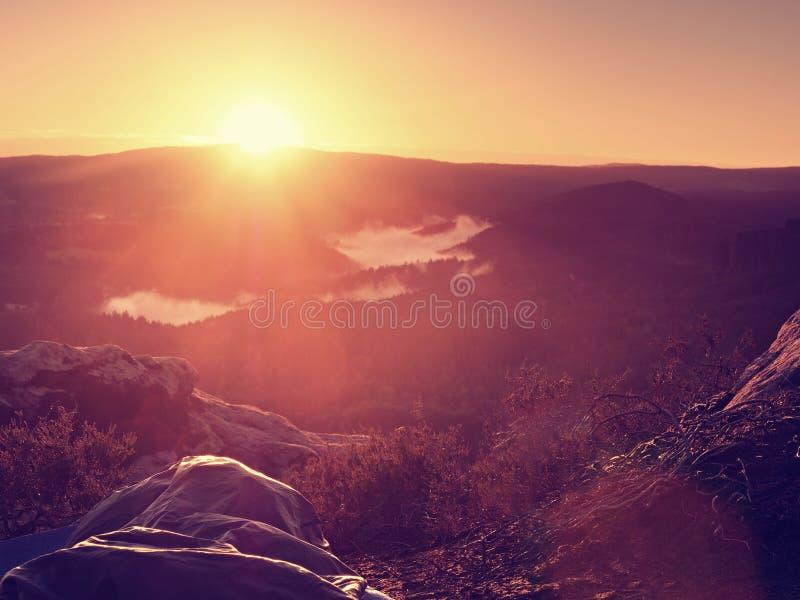 睡觉本质上在睡袋的 美好唤醒在岩石 从岩石峰顶的看法 免版税图库摄影