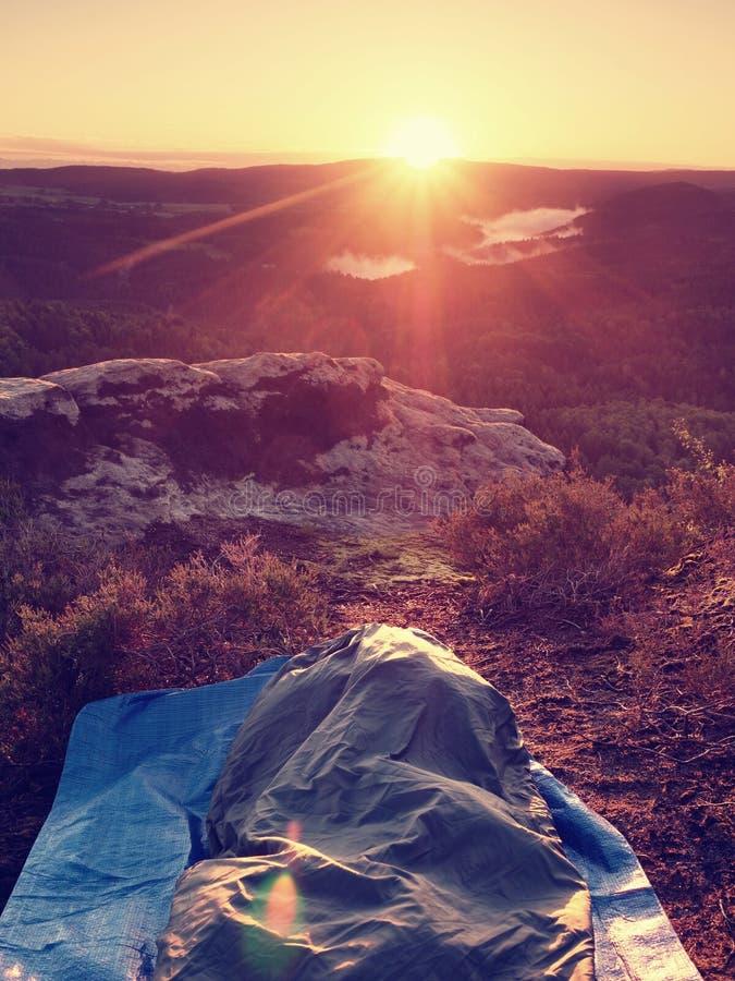 睡觉本质上在睡袋的 美好唤醒在岩石 从岩石峰顶的看法 免版税库存图片
