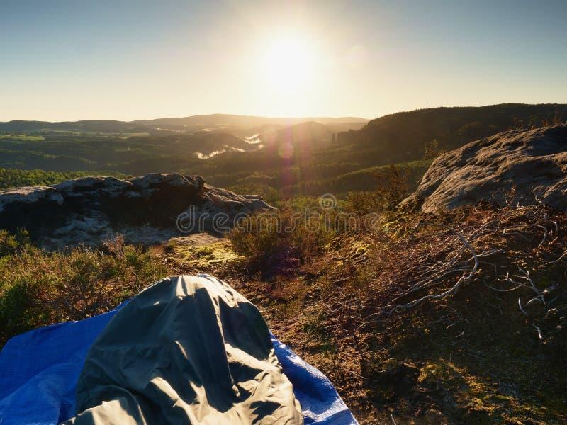 睡觉本质上在睡袋的 美好唤醒在岩石 从岩石峰顶的看法 免版税库存照片