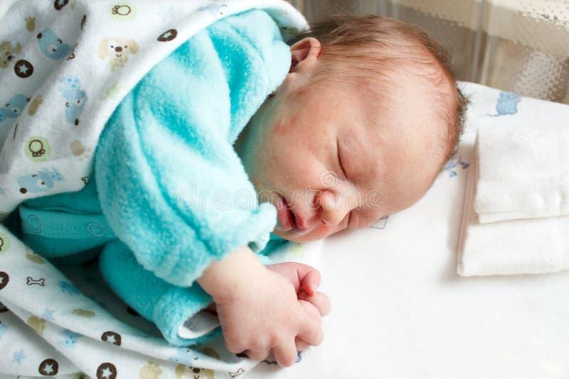 睡觉用手的新出生的婴孩被折叠 免版税图库摄影