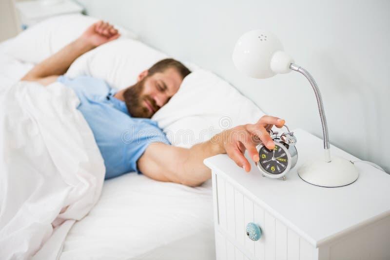 睡觉的人由在床上的一个警报唤醒了 免版税库存照片