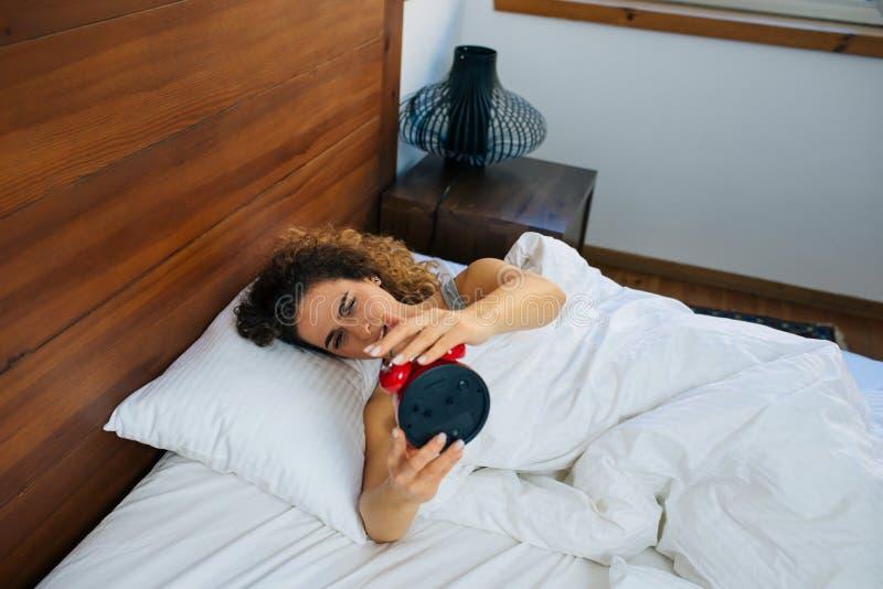 睡觉的妇女和早晨醒关闭闹钟 库存照片