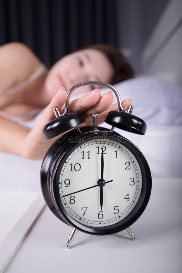 睡觉的妇女和醒关闭在mornin的闹钟 图库摄影