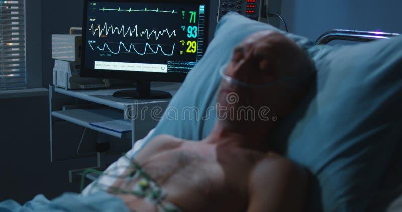 睡觉的患者和心脏监护器 图库摄影