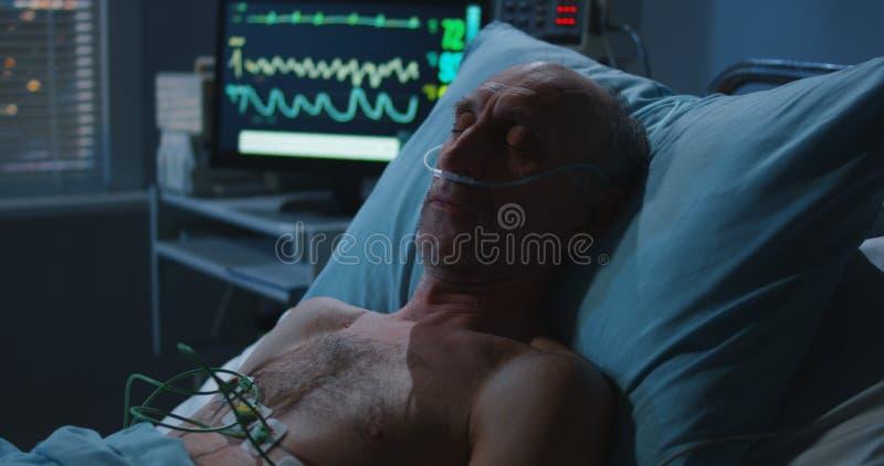 睡觉的患者和心脏监护器 免版税库存照片