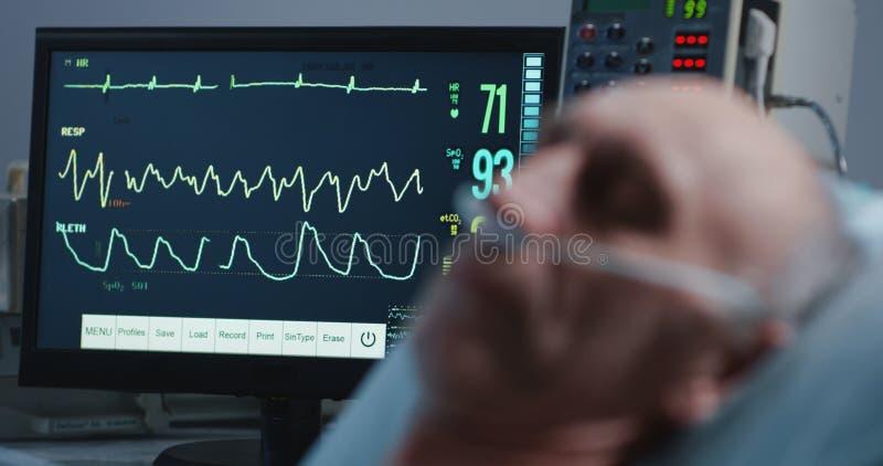 睡觉的患者和心脏监护器 库存图片