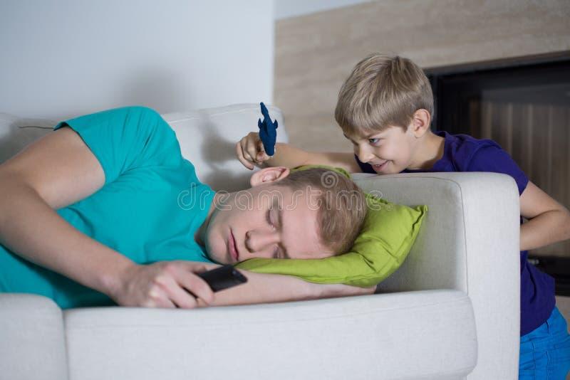 睡觉的爸爸对他的儿子不关心 免版税库存图片
