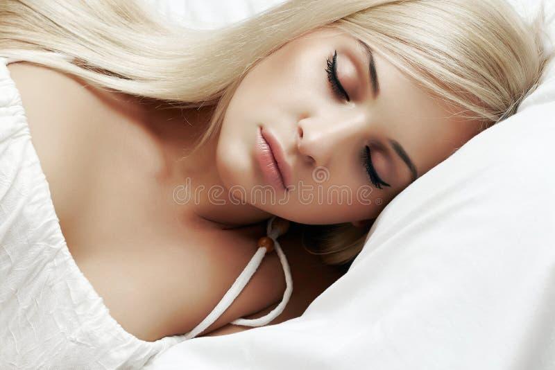 睡觉的美丽的白肤金发的妇女在床上 库存图片