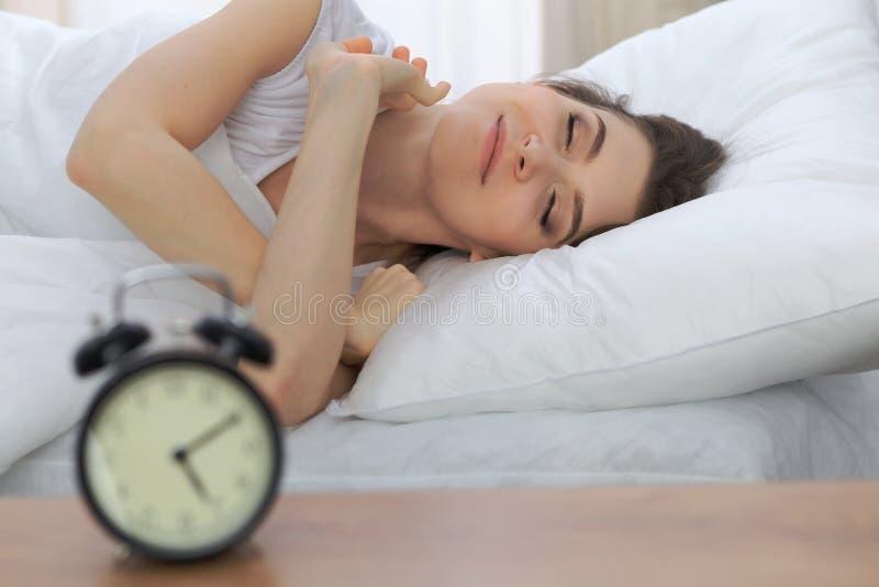 睡觉美丽的少妇,当在她的床上和舒适地时放松 为工作醒或是容易的 免版税库存图片