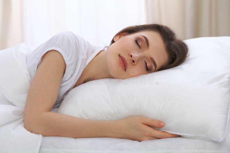睡觉美丽的少妇,当在她的床上和舒适地时放松 为工作醒或是容易的 免版税图库摄影