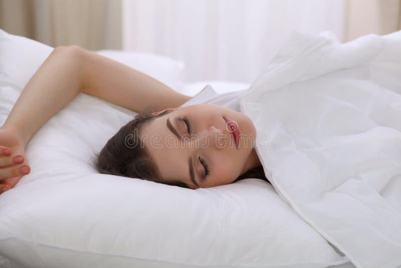 睡觉美丽的少妇,当在她的床上时 宜人和休息复原的概念为活跃生活 库存照片