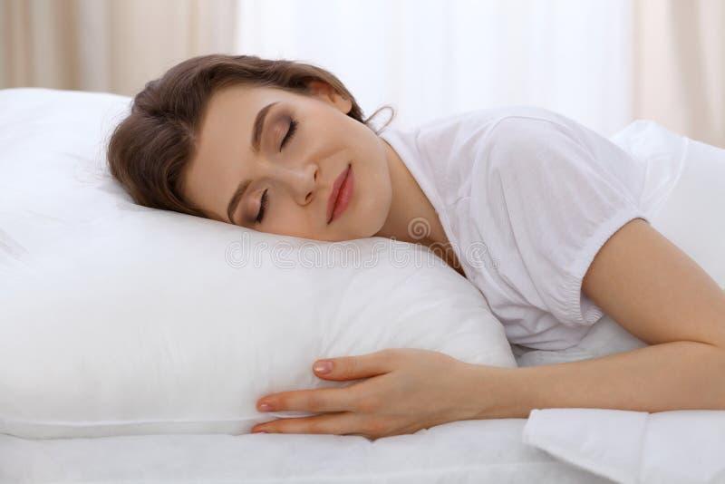 睡觉美丽的少妇,当舒适地和有福地时在床上 清早,您为工作醒或 库存照片