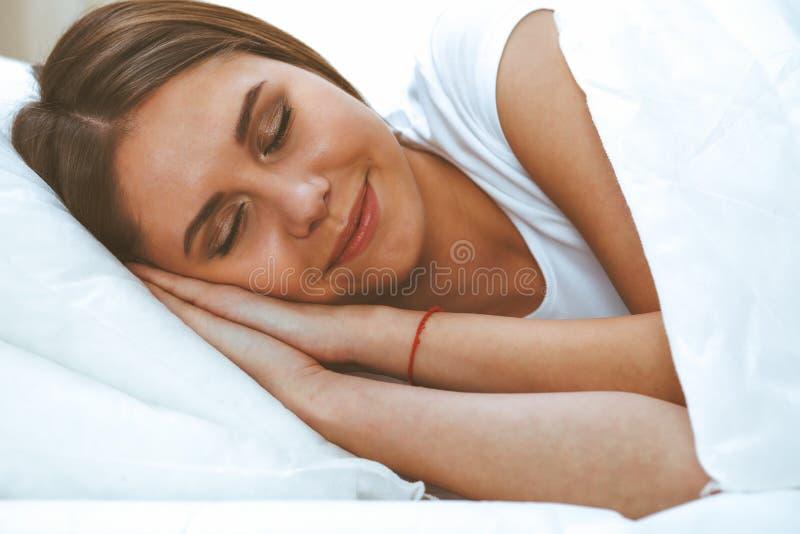 睡觉美丽的年轻和愉快的妇女,当舒适地在床上和有福地微笑时 免版税库存照片