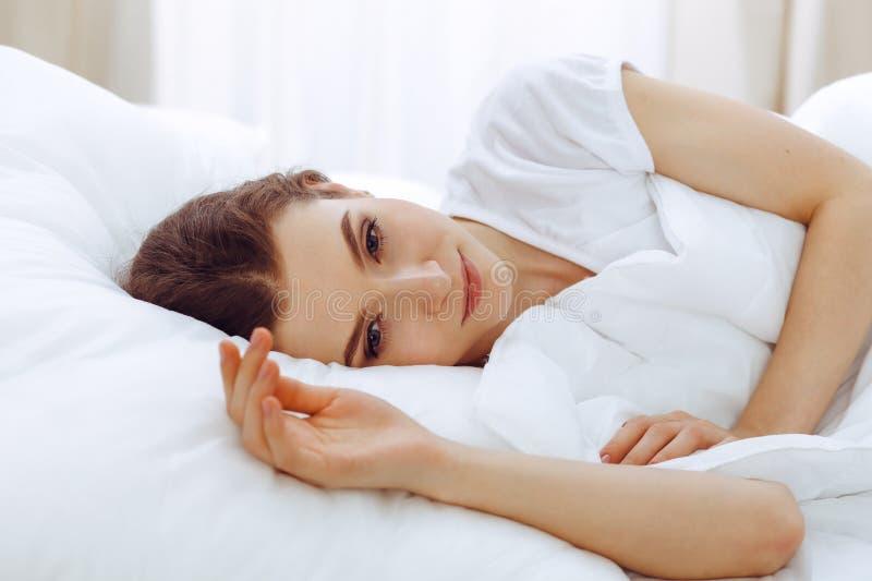 睡觉美丽的年轻女人,当在她的床上时 宜人和休息复原的概念为活跃生活 库存图片