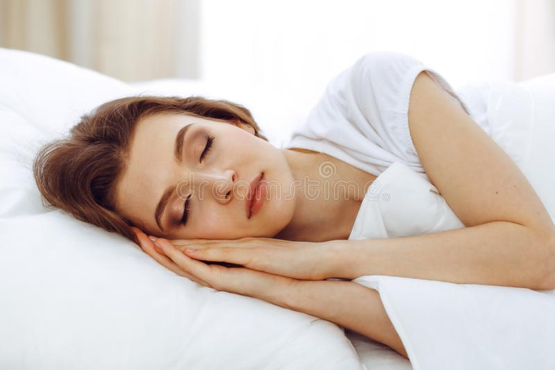 睡觉美丽的年轻女人,当在她的床上时 宜人和休息复原的概念为活跃生活 免版税库存照片