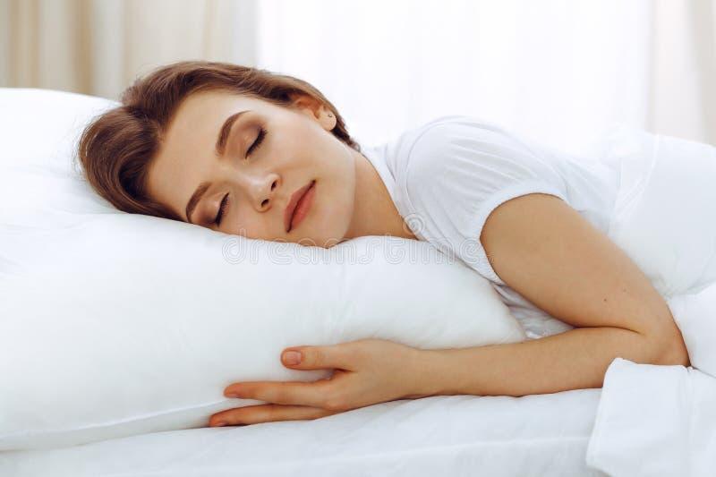 睡觉美丽的年轻女人,当在她的床上时 宜人和休息复原的概念为活跃生活 免版税图库摄影