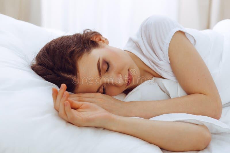 睡觉美丽的年轻女人,当在她的床上时 宜人和休息复原的概念为活跃生活 免版税库存图片