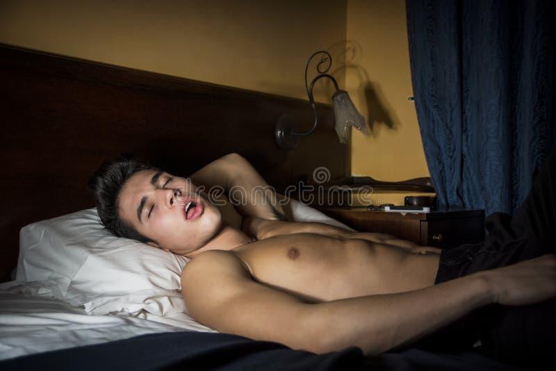 睡觉英俊的赤裸上身的运动年轻的人  免版税图库摄影