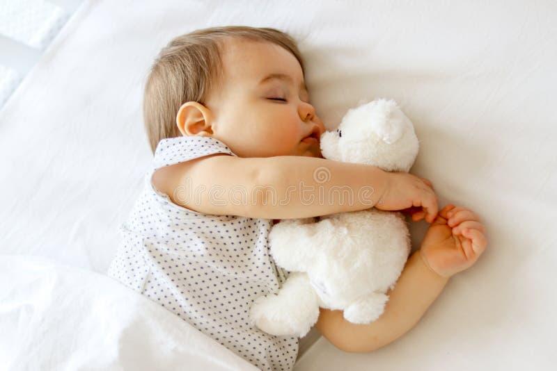睡觉逗人喜爱的矮小的婴孩拥抱他的白色玩具熊 库存图片