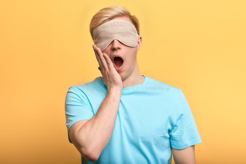 睡觉面具的年轻人与在打呵欠他的嘴的plam 免版税库存照片