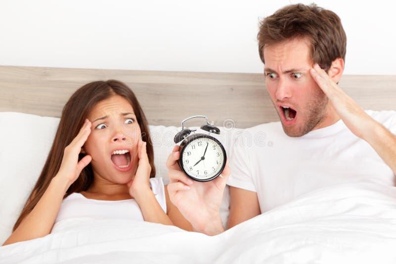睡过头-恐惧的夫妇睡过头了 图库摄影