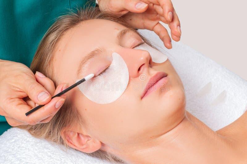 睫毛关心治疗做法 做睫毛分片,弄脏,卷曲,碾压和引伸鞭子的妇女 库存照片
