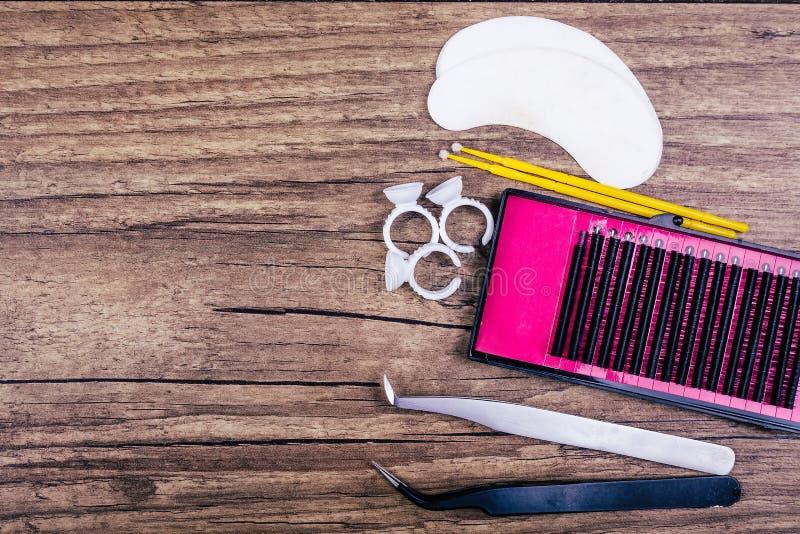 睫毛在木背景的引伸工具 睫毛引伸的辅助部件 人为鞭子 顶视图 库存照片