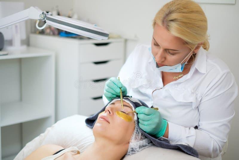 睫毛引伸做法在沙龙的由化妆师 免版税库存图片