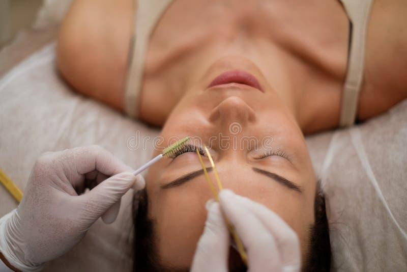睫毛引伸做法在沙龙的由化妆师 库存图片