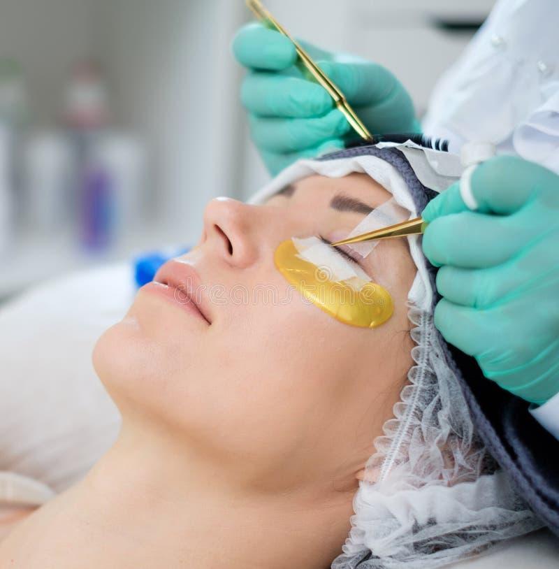 睫毛引伸做法在沙龙的由化妆师 免版税库存照片