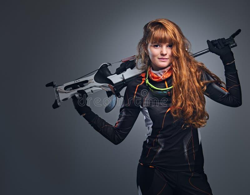 瞄准与一杆竞争枪的红头发人女性两项竞赛冠军 库存图片
