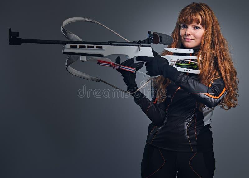 瞄准与一杆竞争枪的红头发人女性两项竞赛冠军 免版税库存图片