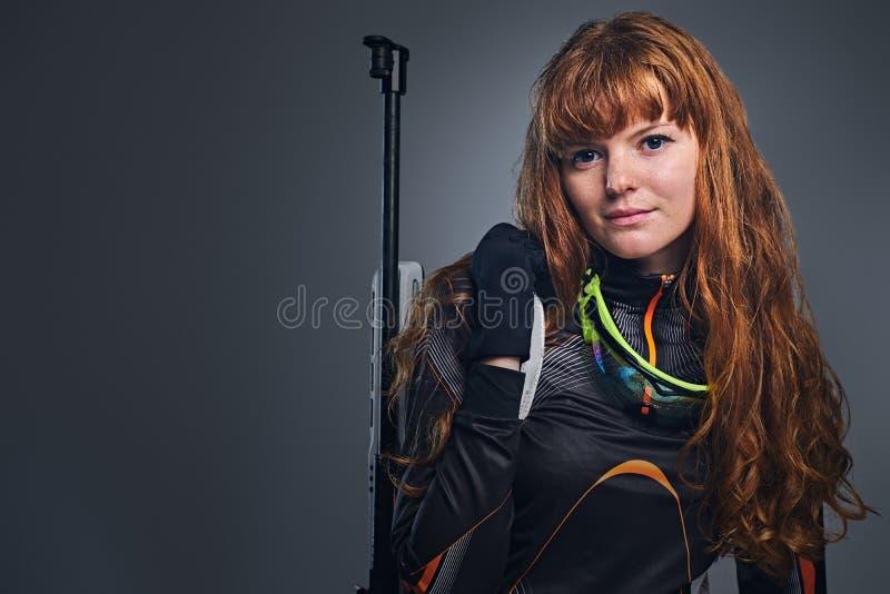 瞄准与一杆竞争枪的红头发人女性两项竞赛冠军 免版税图库摄影