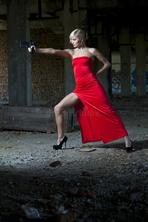 瞄准与枪的减速火箭的看起来的妇女 免版税库存照片