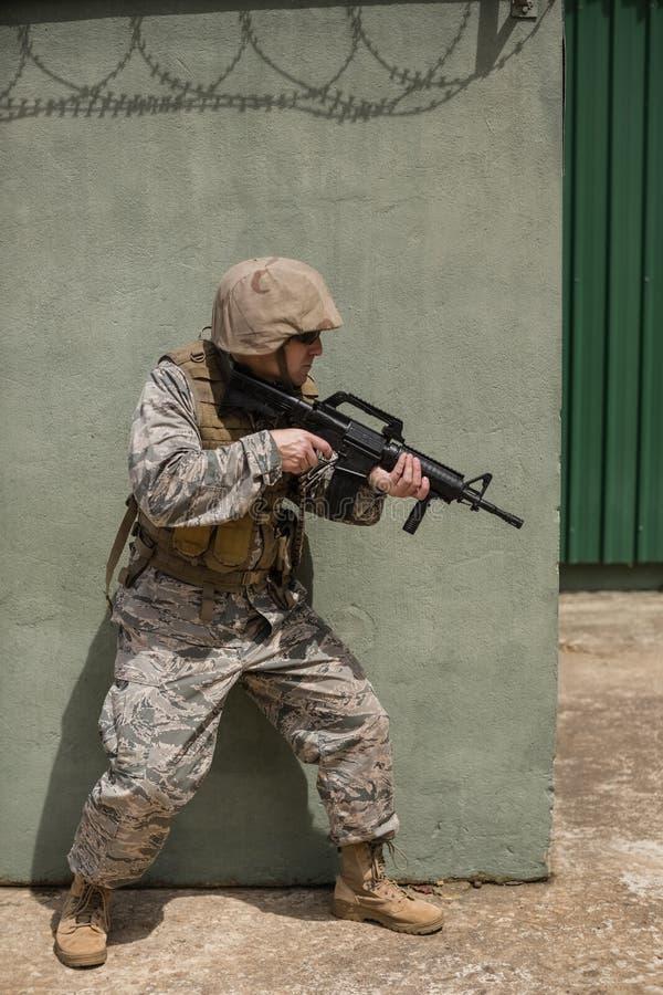 瞄准与步枪的军事战士对混凝土墙 免版税库存图片