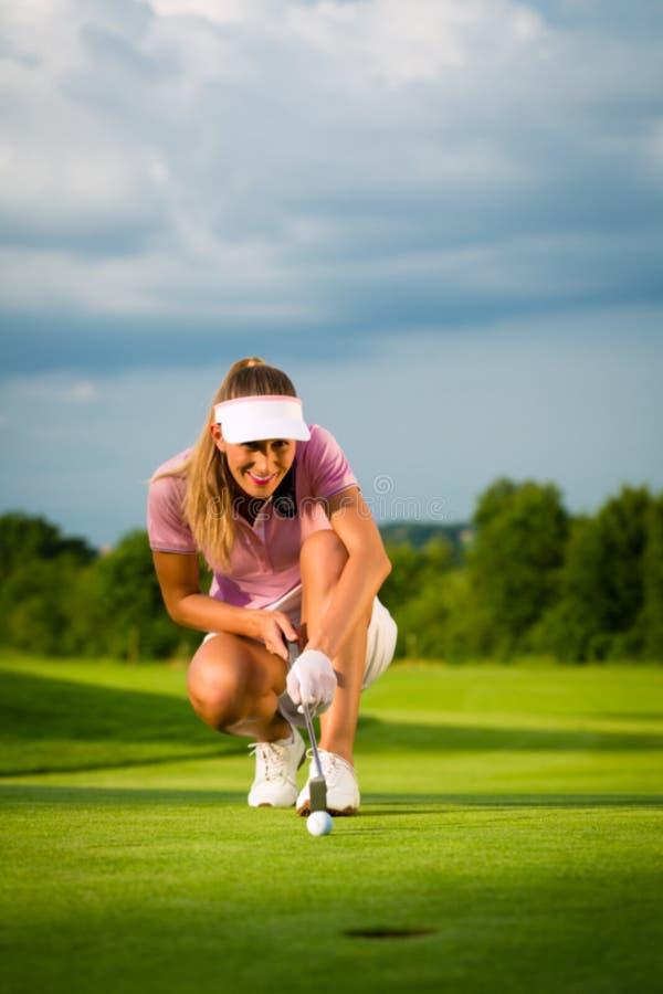 瞄准为她的路线的年轻女性高尔夫球运动员投入了 免版税库存图片