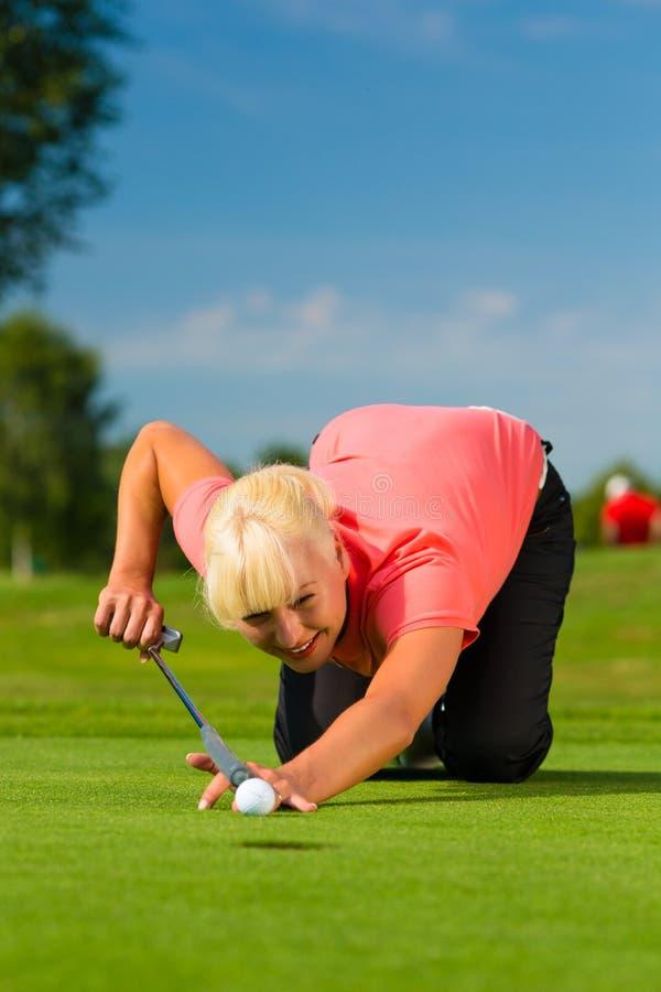 瞄准为投入的路线的年轻女性高尔夫球运动员 免版税库存照片