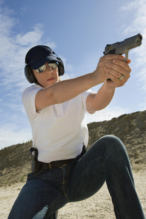 瞄准手枪的妇女射击距离 免版税库存图片