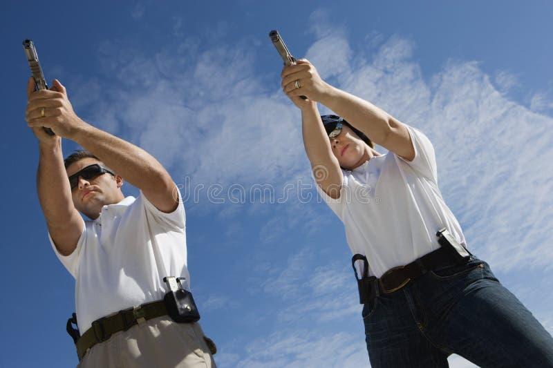 瞄准手枪的男人和妇女射击距离 免版税库存图片