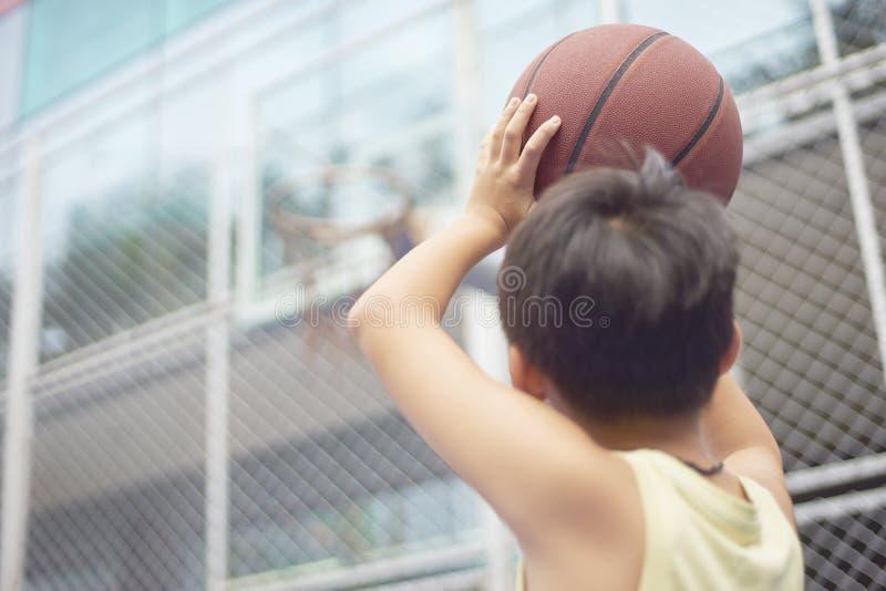 瞄准篮球篮的男孩背面图在射击前 图库摄影