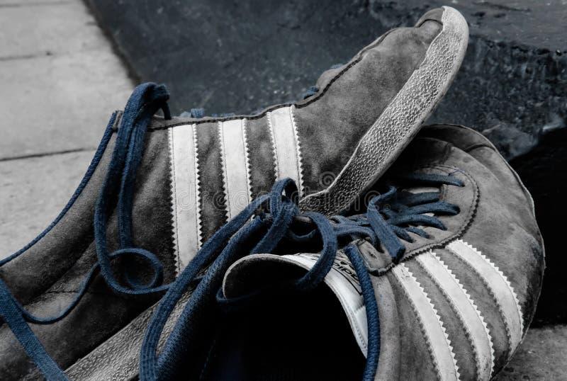 知名的体育衣物和制鞋商,显示在门廊之外的穿的鞋子 图库摄影