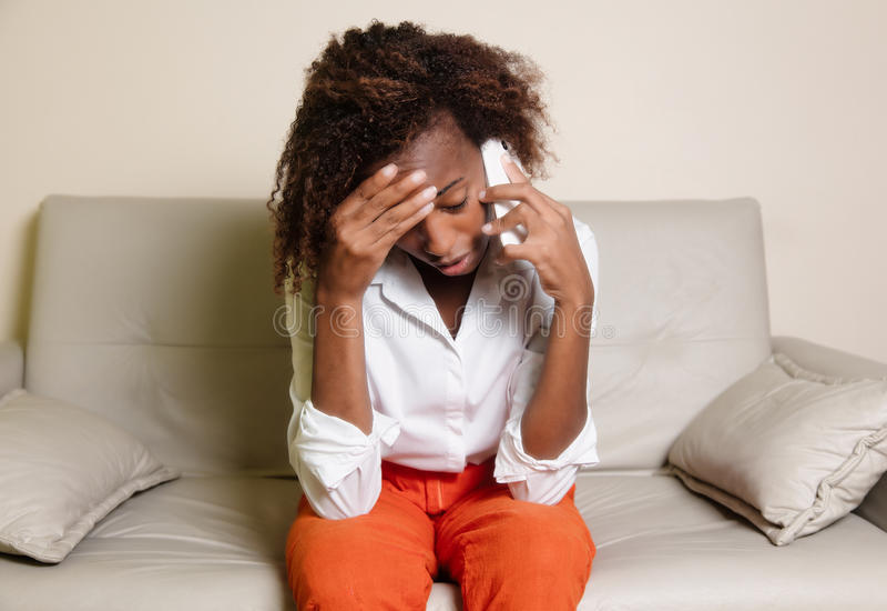 知道坏消息的震惊非裔美国人的妇女在电话 免版税库存图片