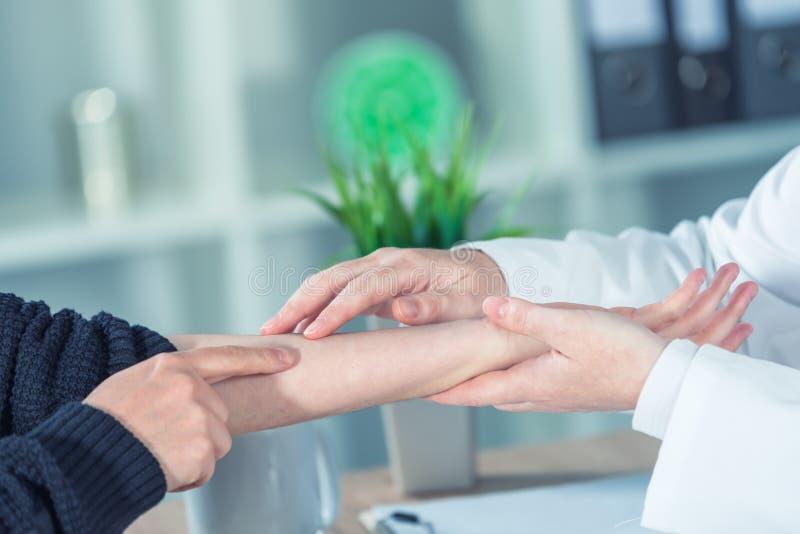 矫形医生身体检查的女性患者腕子injur的 免版税库存图片