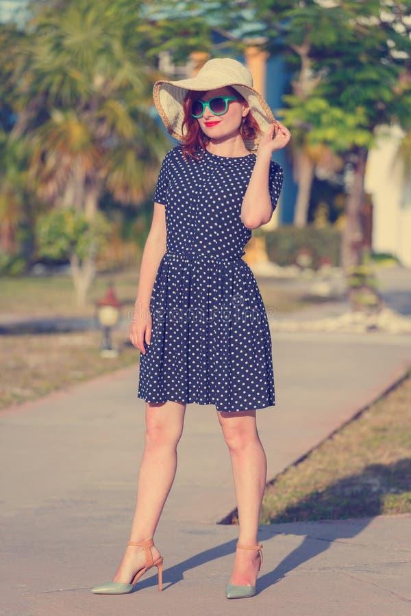 短上衣小点礼服和草帽的少妇 免版税库存图片
