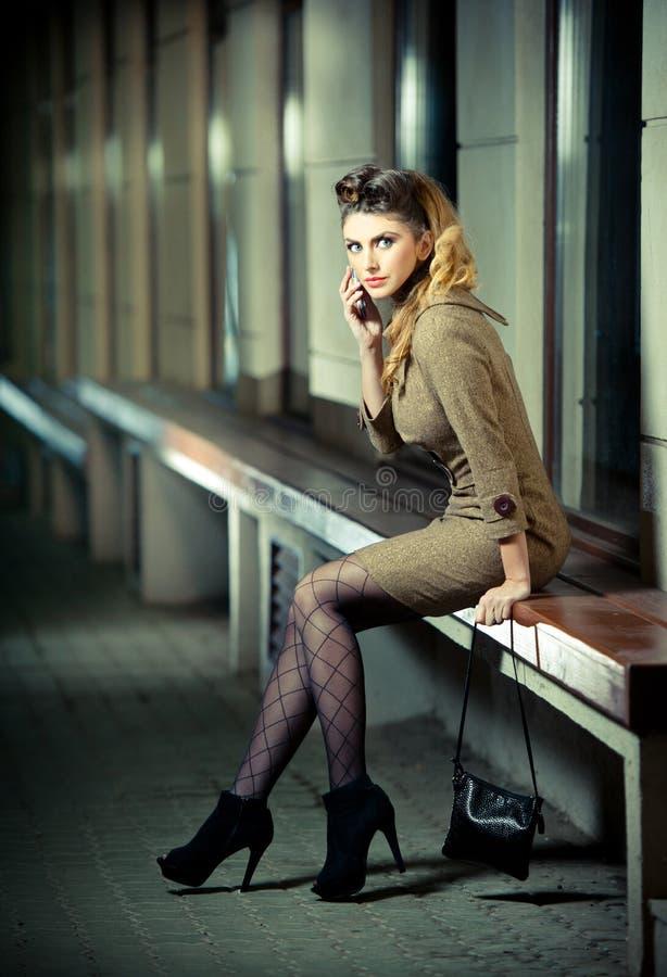 短小佩带礼服和高跟鞋-都市场面的可爱的白肤金发的女孩。与长的性感的腿的时装模特儿坐长凳 库存图片