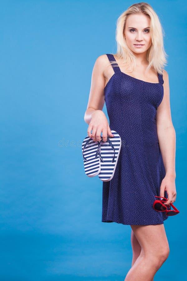 短小穿礼服的妇女拿着触发器和太阳镜 图库摄影