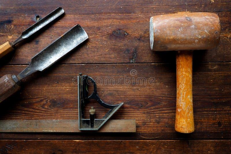 短槌和三角板与木凿在老台式 免版税库存图片